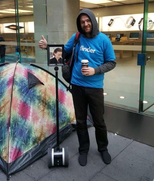 """Las personas que hacen fila afuera de una tienda de Apple en Australia aprovechan el momento para tomarse una foto con el robot """"Lucy"""". (Foto: Mashable)"""