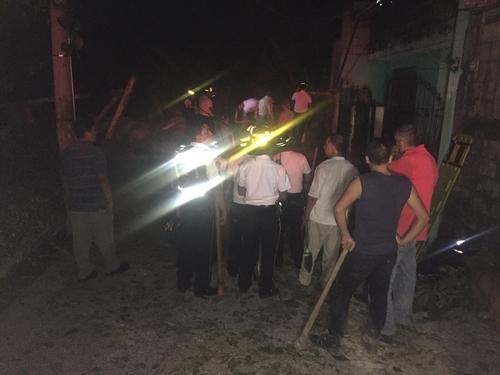 Bomberos y vecinos trabajan en el rescate de las personas que se encontraban en el interior de las 15 viviendas afectadas por el derrumbe en la aldea El Cambray II, Santa Catarina Pinula. (Foto: Bomberos Voluntarios)