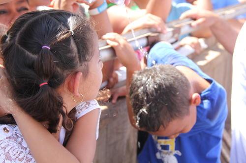 Una niña mira como se refresca su amigo por las altas temperaturas. (Foto: Roberto Caubilla/Soy502)