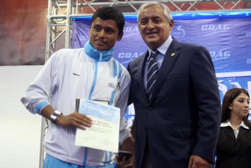 El medallista olímpico Erick Barrondo recibe el premio económico de su medalla de oro en los Juegos Bolivarianos 2013, de manos del presidente Otto Pérez Molina. (Foto: Luis Barrios/Soy502)