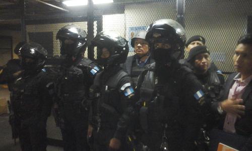"""Un grupo de agentes de la PNC resguarda a Salvador González alias """"Eco"""" durante su traslado el miércoles 16 de diciembre a la Torre de Tribunales. (Foto: Evelyn de León/Soy502)"""