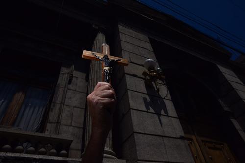 Nicolás Carrera, de 77 años, sostiene una cruz y pide se lleve a cabo la sesión del Congreso. (Foto Jesús Alfonso/Soy502)