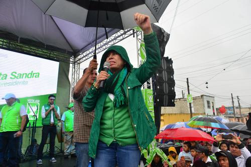 Su personal de seguridad estuvo sosteniendo sin interrupción la sombrilla para que no se mojara la candidata. (Foto: Jesús Alfonso/Soy502)