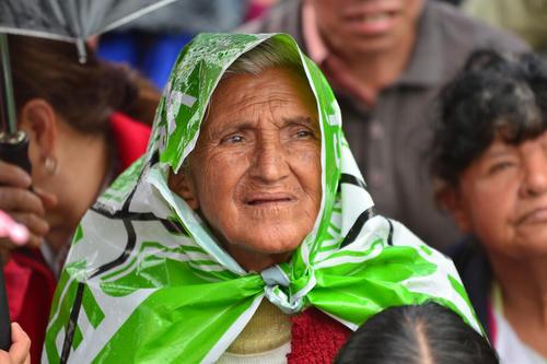 La lluvia estuvo presente durante todo el acto y los asistentes se las ingeniaron para cubrirse. (Foto: Jesús Alfonso/Soy502)