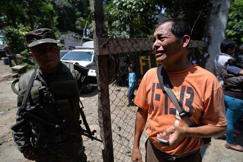 Joel Contreras habla por teléfono con su esposa y pide a los elementos del Ejército colaboración para localizar a su familia.  (Foto: Wilder López/Soy502)