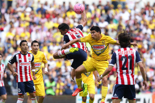 El jugador de América, Luis Ángel Mendoza, disputa el balón con Patricio Gabriel Araujo, de Chivas de Guadalajara.