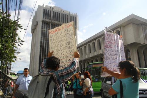 """Dos manifestantes levantaron pancartas exigiendo la renuncia de Otto Pérez y se mostraron indignados con el despliegue de seguridad. """"Solo en este país, la policía cuida a los ladrones"""", dijo la mujer. (Foto: Alexis Batres/Soy502)"""