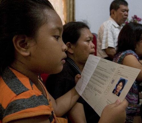 Esta niña observa los documentos de su tía Suri Dahlia quien viajaba en el vuelo desaparecido. (Foto:AFP)