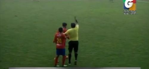 Ever López busca a Carlos Ruiz para mostrarle la tarjeta amarilla y el jugador reacciona.