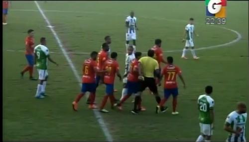 Dos jugadores de Municipal tratan de frenar la carrera de varios metros del árbitro,  Ever López, quien va sobre Carlos Ruiz, para mostrarle la tarjeta roja.