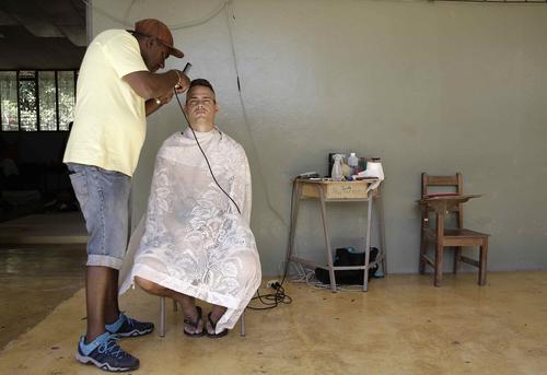 Muchos cubanos tienen el dinero para seguir su camino, porque lo reciben de familiares en Estados Unidos. Los que no tienen esa suerte intentan trabajar dentro del albergue en lo que puedan, como cortando el pelo a los que emprenderán el viaje este martes. (Foto: EFE)