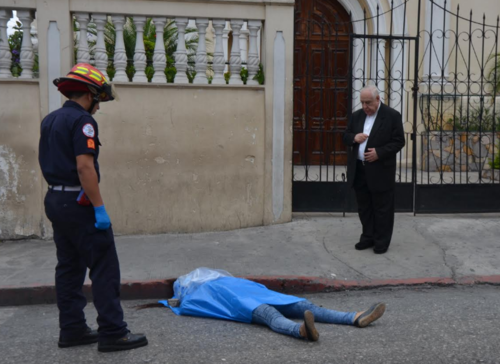 El sacerdote reza frente al cuerpo de la mujer asesinada. (Foto: Cortesía Bomberos Municipales)