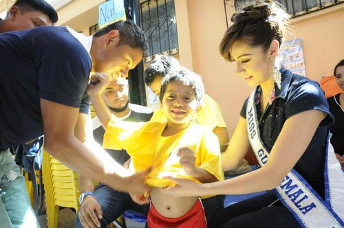 Miss Guatemala 2015-2016, Jeimmy Aburto y el seleccionado nacional, Carlos Mejía, visten a un pequeño niño en el albergue del Salón Municipal de Santa Catarina Pinula, donde se encuentran los damnificados del Cambray II. (Foto: Orlando Chile)