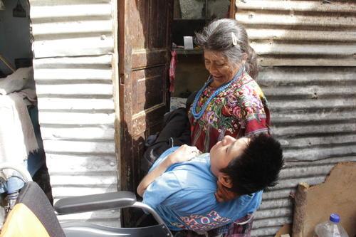 Doña Julita aún tiene fuerzas para cargar a su hijo y llevarlo de la silla de ruedas a la cama y viceversa. Pero requiere el apoyo de los guatemaltecos de buen corazón para que pueda atender con mayor facilidad a su hijo. (Foto: Fredy Hernández/Soy502)