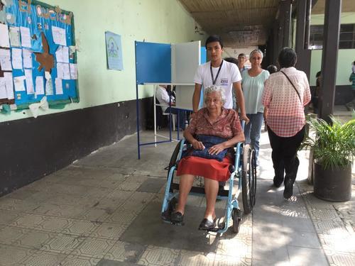 Voluntarios en los centros electorales ayudan a personas con discapacidad, a movilizarse dentro de los centros electorales. (Foto: Soy502/Marcela Fernández)
