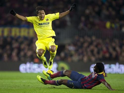 El delantero mexicano del Villarreal, Giovani Dos Santos y el camerunés del Barcelona, Alexandre Song luchan por el balón. (Foto: EFE)
