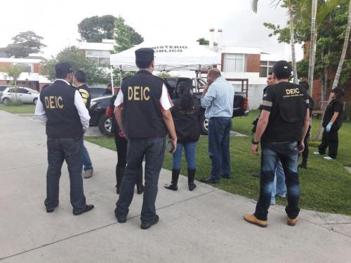 El abogado Benjamin Estrada conversa con fiscales del MP mientras su vehículo es revisado. (Foto: PNC)