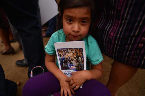 Entre los niños que estaban en el mitin fueron repartidos cuadernos con la imagen de Jimmy Morales. (Foto: Wilder López/Soy502)