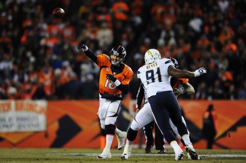 Peyton Manning realiza un pase ante la presión de Kendall Reyes