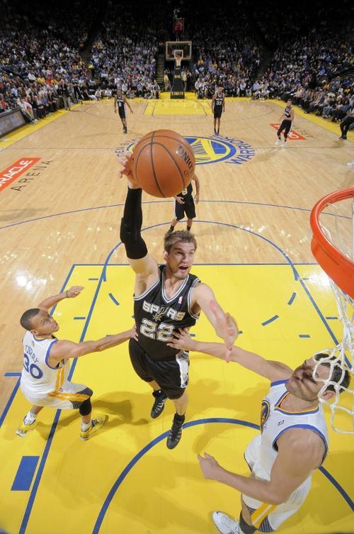 Tiago Splitter anota para los Spurs de San Antonio ante la marca de Andrew Bogut de los Warrios de Golden State