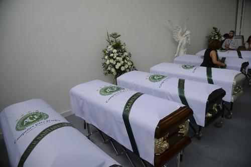 Imagen de varios ataúdes de los futbolistas fallecidos, con el escudo del equipo. (Foto: AFP)
