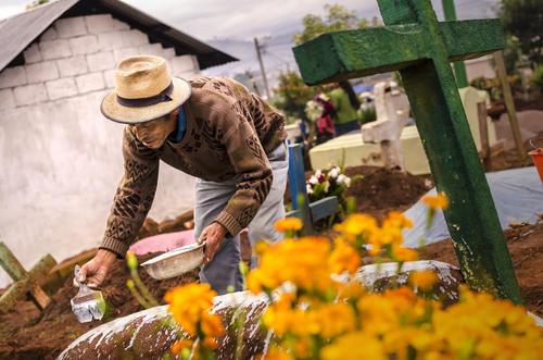 Un vecino de Sumpango decorando una tumba por la mañana