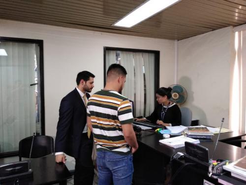 El integrante de la banda y su otro abogado, Carlos Moscoso, mientras esperaban el permiso para salir del país. (Foto: Soy502)