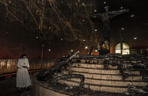 Una religiosa camina cerca del altar donde explotó la bomba que atentó con la histórica imagen. (Foto: AFP)