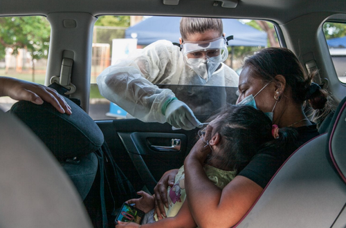 Una madre toma a su hija mientras toma una prueba por Covid-19.  (Foto: Cindy Karp/The Washington Post)