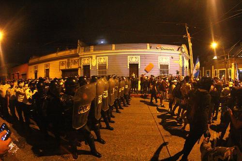 Un grupo de manifestantes pacíficos se colocó frente a los antimotines para que los otros, a quienes señalaron de infiltrados, no los provocaran. (Foto: Alexis Batres/Soy502)