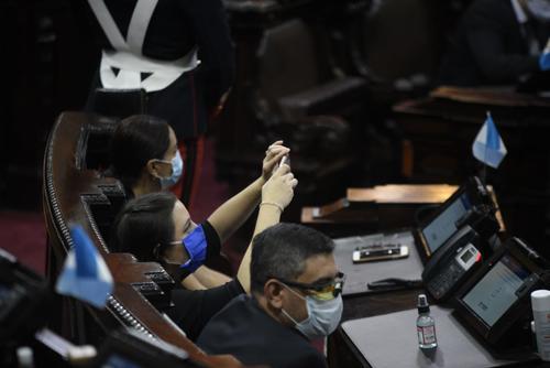 Las diputadas Andrea Villagrán y Evelyn Morataya se toman selfies durante el discurso de Alejandro Giammattei. (Foto: Wilder López/Soy502)