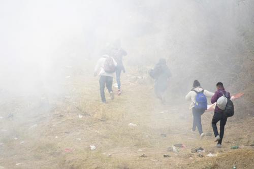 Migrantes se alejan del gas lacrimógeno. (Foto: AFP)