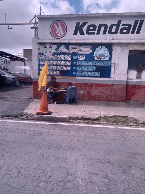 En las imágenes se observa que la mujer ayuda con las tareas a sus hijos en la calle.