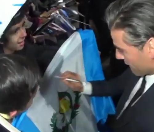 "Oscar Isaac signing a Guatemalan flag at the premiere of ""Star Wars Episode VII: The Force Awakens �.  (Photo: Screenshot)"