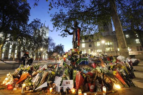 Decenas de ciudadanos han dejado flores y regalos a la estatua de Nelson Mandela frente al Parlamento en Londres. (Foto: Facundo Arrizabalaga/EFE)