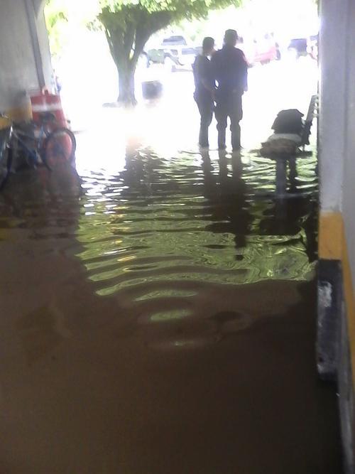 Dos agentes de la PNC se encuentran en las afueras de la Comisaría de Izabal que se inundó por los malos drenajes. (Foto: PDH)