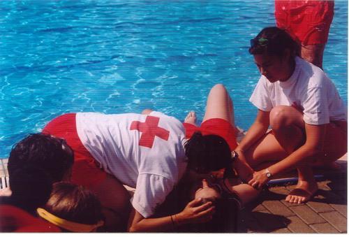 Equipo de cruz roja da primeros auxilios en piscina