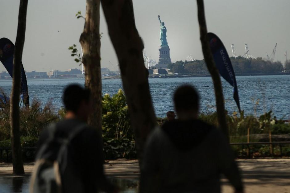 """La gente camina en el """"Battery Park"""", donde se puede tomar un ferry para visitar la Estatua de la Libertad. El monumento turístico también permanece clausurado. Museos federales y parques de todo el país están cerrados por primera vez en casi dos décadas."""