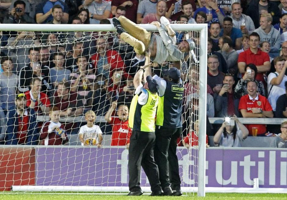 Un aficionado se sostiene de la porteria durante un partido de fútbol en Inglaterra. Se enfrentaron todos los jugadores del Manchester United de la década de 1990 y La clase de 92 estrellas, que eran parte de un consorcio que compró la ciudad de Salford. (Foto: AFP)