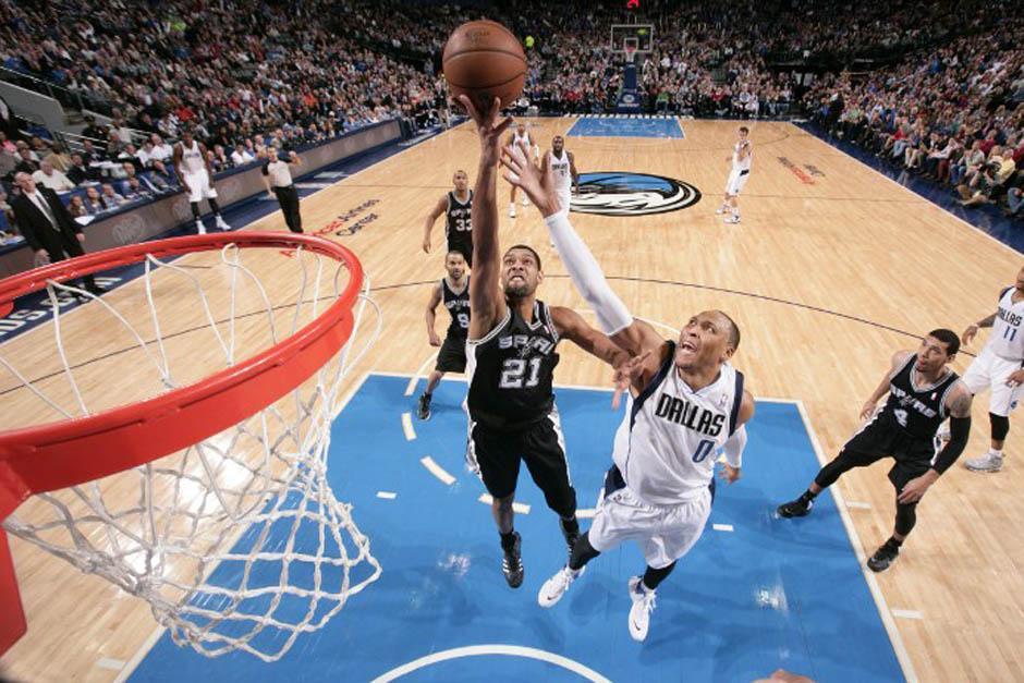 Tim Duncan de los Spurs de San Antonio toma un rebote en una jugada ante Shawn Marion de los Mavericks de Dallas