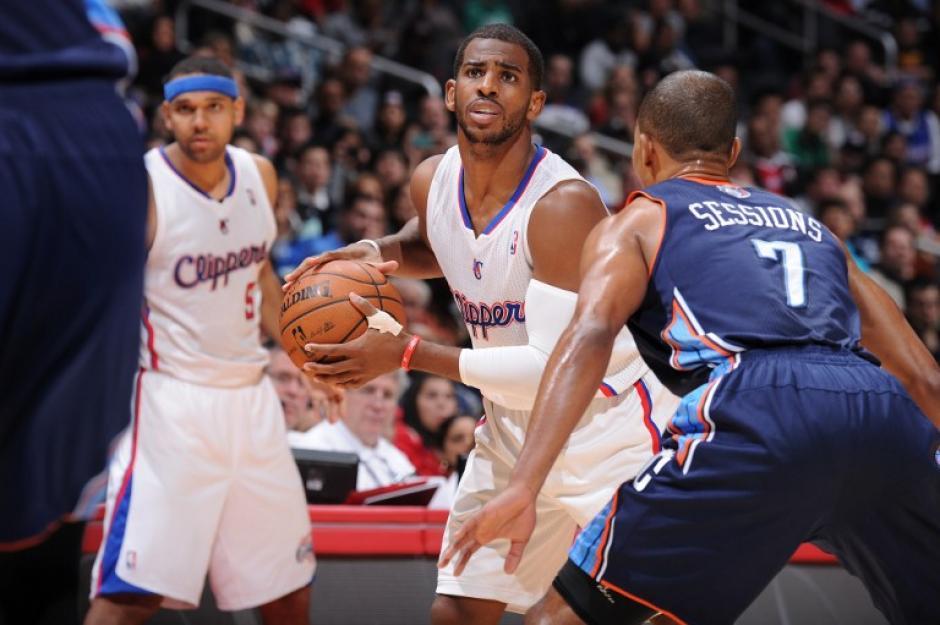 Chris Paul de los Clippers de Los ANgeles maneja el balón ante Ramon Sessions de los Bobcats de Charlotte