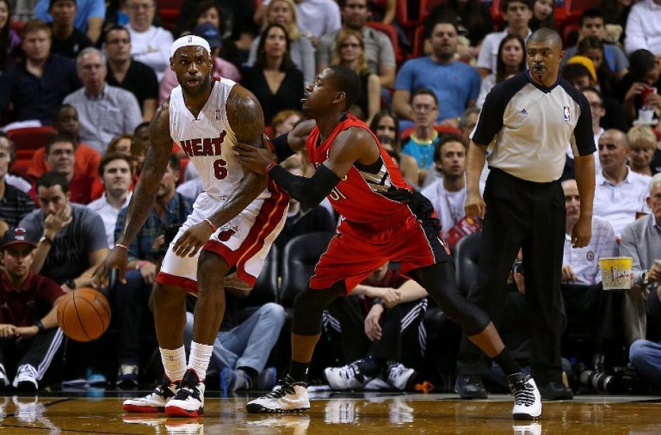 LeBron James guia al Heat de Miami recibe la marca de Terrence Ross de los Raptors de Toronto durante el duelo disputado en el American Airlines Arena. (AFP)