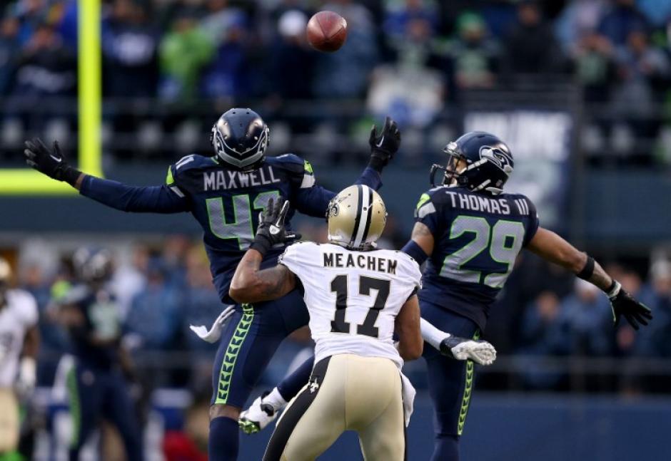 Byron Maxwell (41) y Earl Thomas (29) de los Seahawks de Seattle no logran interceptar un pase para Robert Meachem (17) de los Saints de Nueva Orleans en el cuarto cuarto durante el partido del Playoff de la NFC el sábado. (Foto: AFP)