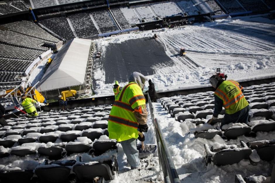 """Las cuadrillas trabajan para quitar la nieve del MetLife Stadium, que será sede de Superbowl XLVIII en East Rutherford, Nueva Jersey. En lo que se llama la primera """"superbowl de clima frío"""". El viento se espera que sea entre los 8 y los 12 kms por hora, lo que podría llegar a afectar el desarrollo del partido. (AFP)"""