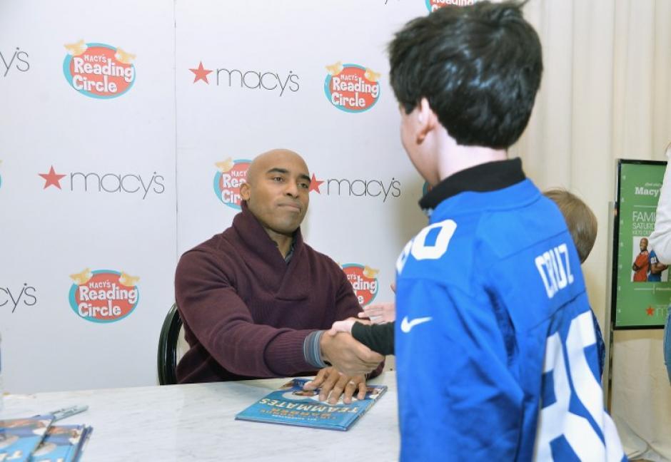 El ex jugador de fútbol profesional Tiki Barber firma ejemplares de su libro mientras celebra el Día de la Familia, en previsión del Super Bowl, en Herald Square de Macy´s en Nueva York.
