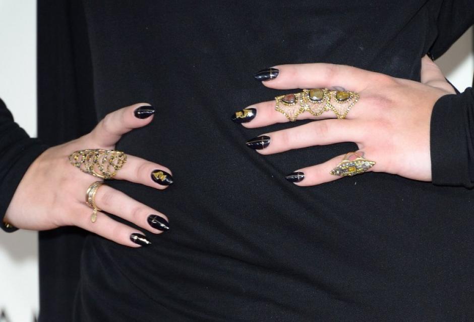 Kelly Osbourne modela sus anillos al entrar a la gala de los Premios Grammy, captando la atención de los fotógrafos. AFP