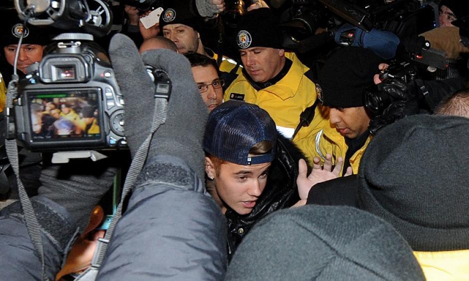 Decenas de guardaespaldas y policías se vieron obligados a emplearse a fondo para contener a la multitud mientras Bieber salía de un vehículo y entraba por una puerta lateral de la comisaria sin decir ni una sola palabra y con la cabeza cubierta por una gorra de béisbol. Foto AFP