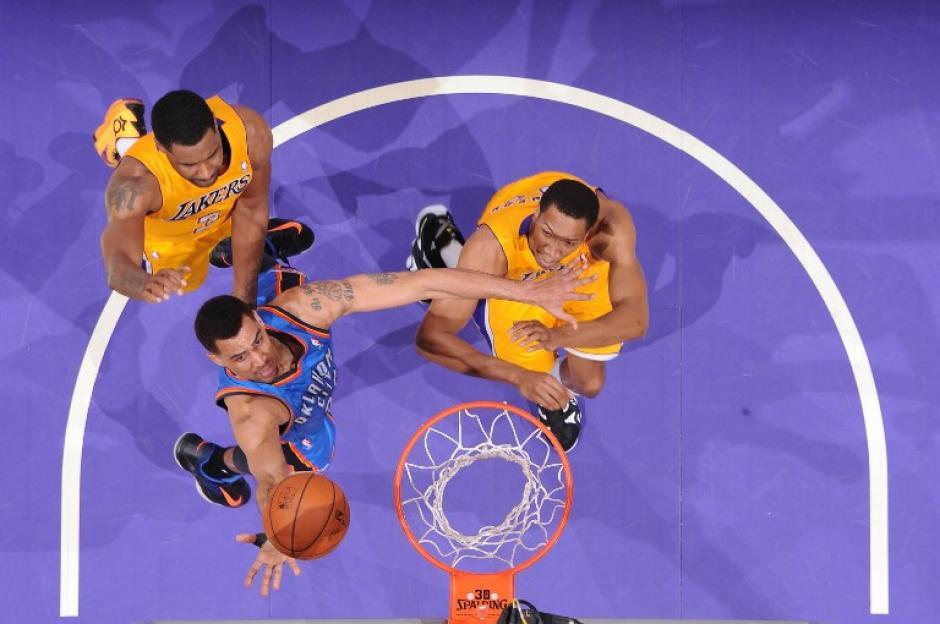 Thabo Sefolosha de los Thunder de Oklahoma City, realiza un tiro ante Shawne Williams  y Wesley Johnson de los Lakers