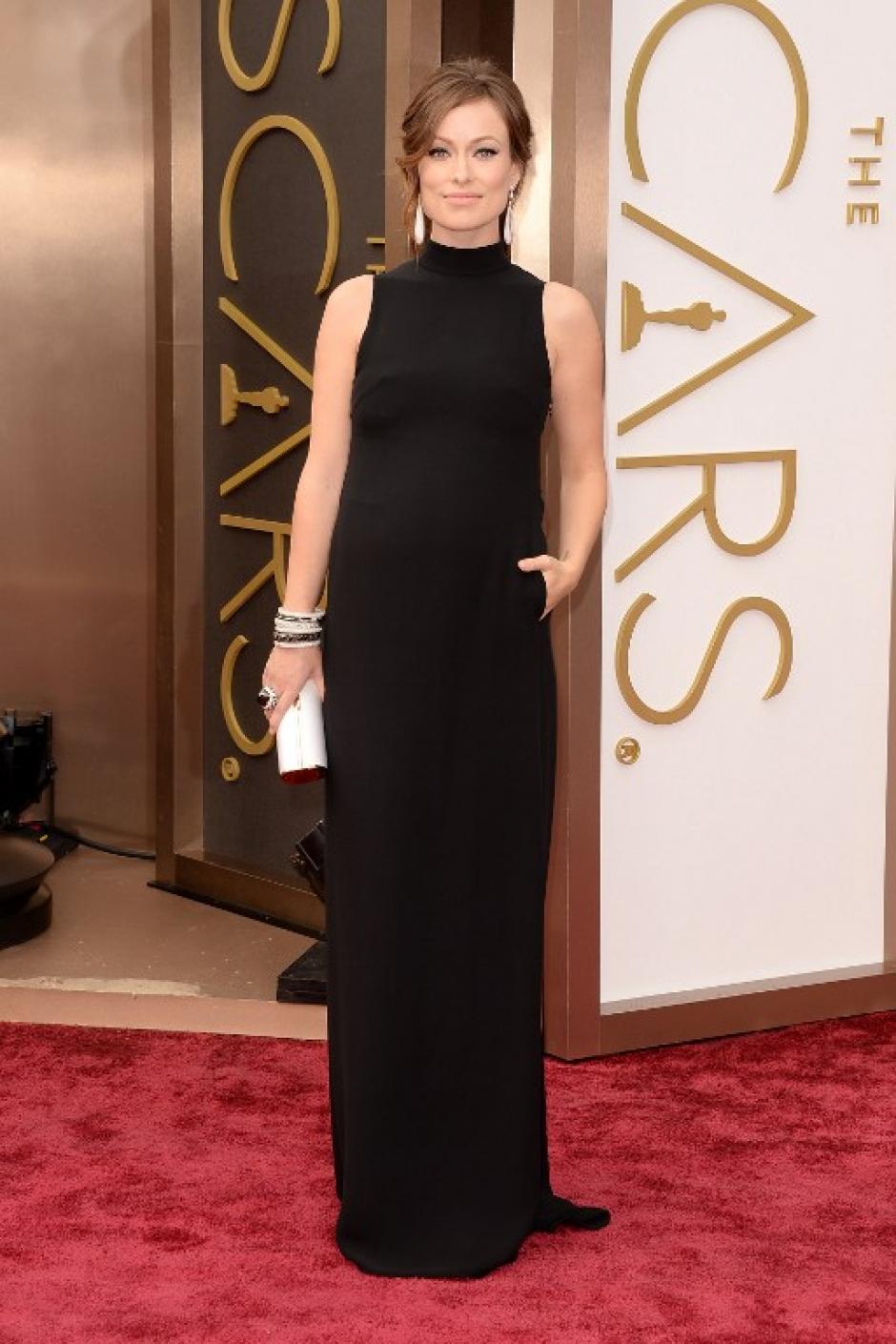"""Olivia Wilde que está embarazada luce un vestido Valentino y una impresionante fila de """"bangles"""" cargadas de diamantes en el brazo derecho. (Foto: AFP)"""