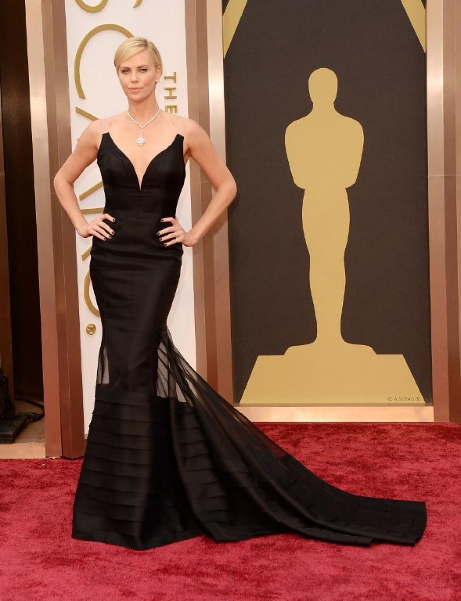 Charlize Theron llega con un vestido negro con un pronunciado escote y transparencias. (Foto: AFP)